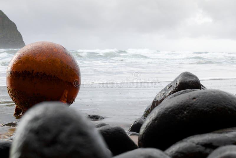 在岩石灰色海滩的橙色浮体 库存照片