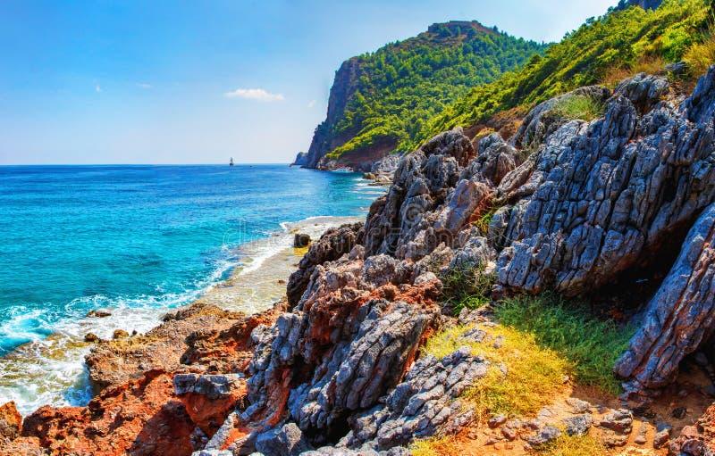 在岩石热带海滩的惊人的看法在晴朗的夏日在土耳其 与山和岩石的土耳其海景在海岸线 图库摄影