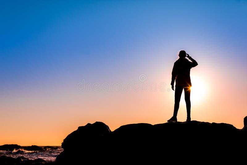 在岩石的上面a的妇女 免版税库存照片