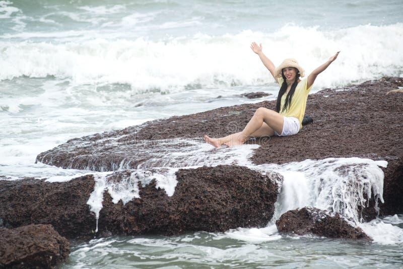 在岩石的亚洲俏丽的女性开会充满强的波浪和放松幸福 库存照片