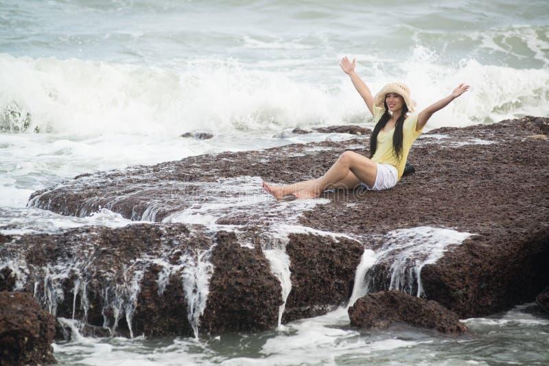 在岩石的亚洲俏丽的女性开会充满强的波浪和放松幸福 免版税库存照片