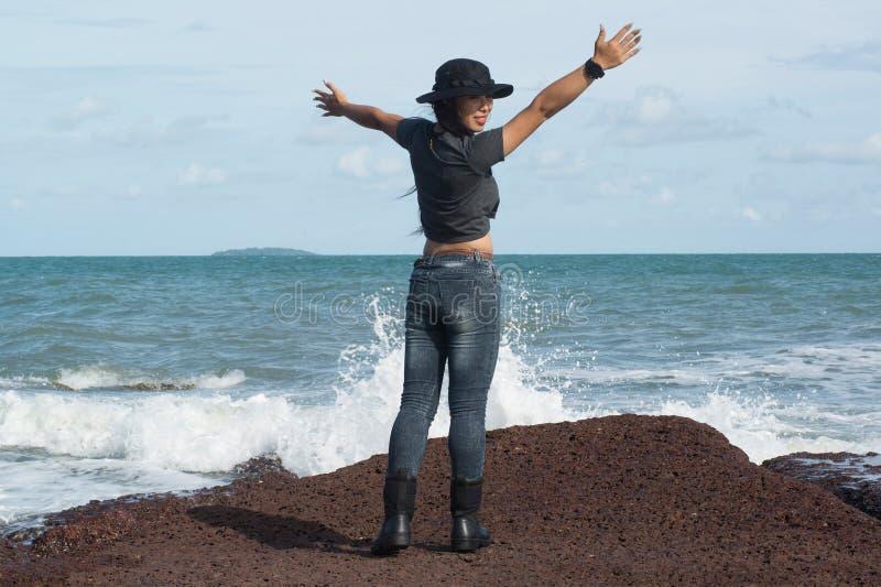 在岩石的亚洲俏丽的女性身分与强的波浪 免版税库存图片