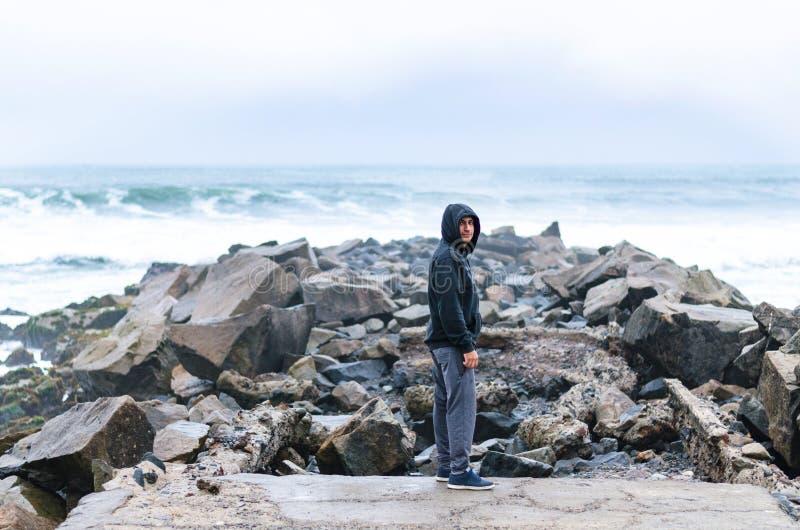 在岩石的人身分在海洋中间 免版税库存图片