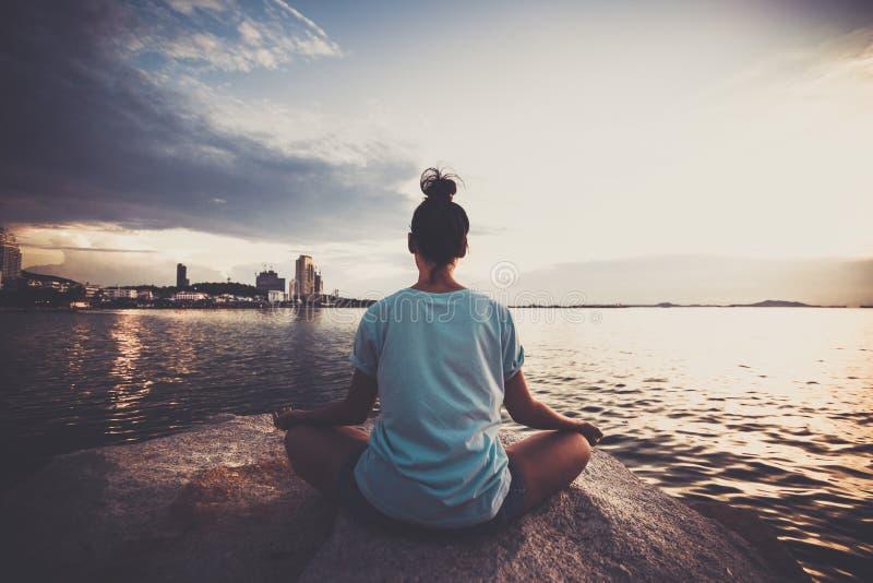 在岩石的女子瑜伽在有日落天空的海附近 库存照片