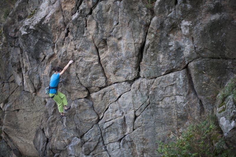 在岩石的女孩攀登 免版税库存照片