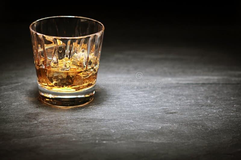 在岩石的威士忌酒在玻璃翻转者 免版税库存图片