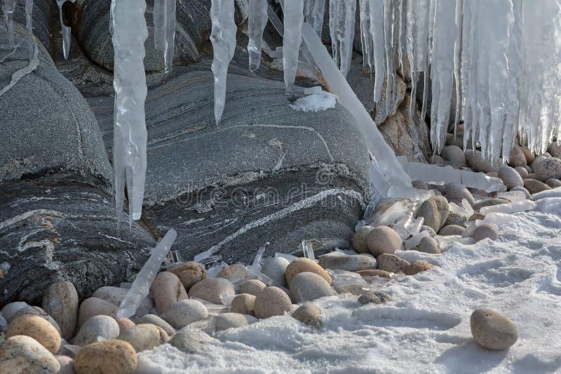 在岩石的巨大的冰柱 美好的冬天风景在贝加尔湖 免版税库存图片
