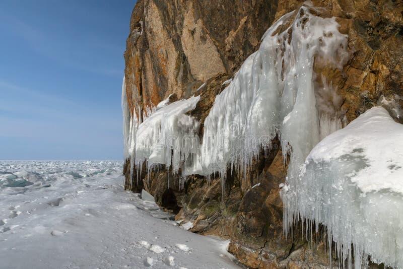 在岩石的巨大的冰柱 美好的冬天风景在贝加尔湖 免版税图库摄影