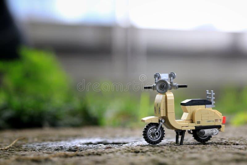 在岩石的微型米黄色的葡萄酒摩托车玩具停车处 免版税库存图片