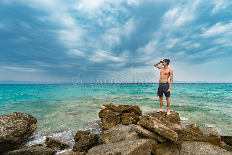 在岩石的旅客赤裸上身的身分在很远注视着天际的海附近 免版税库存照片