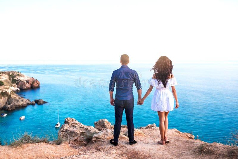 在岩石的浪漫夫妇在美丽的海海滩附近 免版税图库摄影