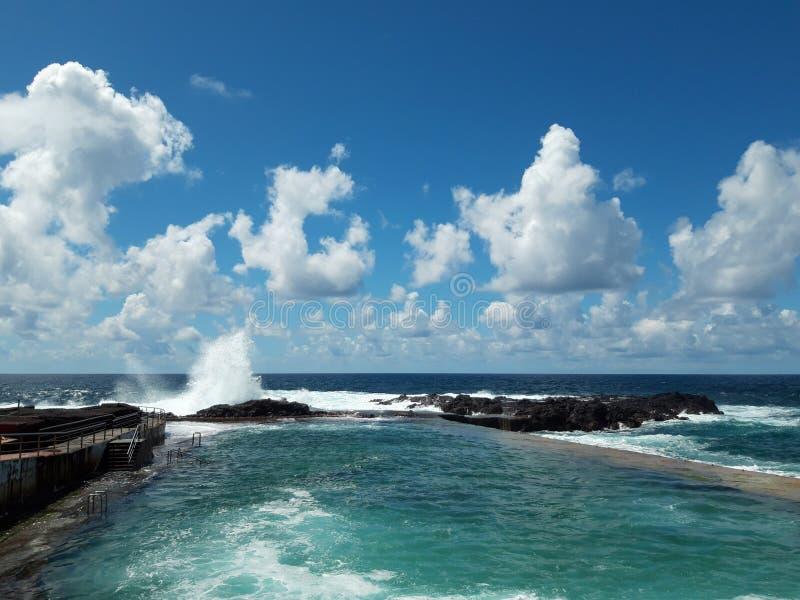 在岩石的海浪飞溅在海岸在与天空蔚蓝的一好日子 库存照片
