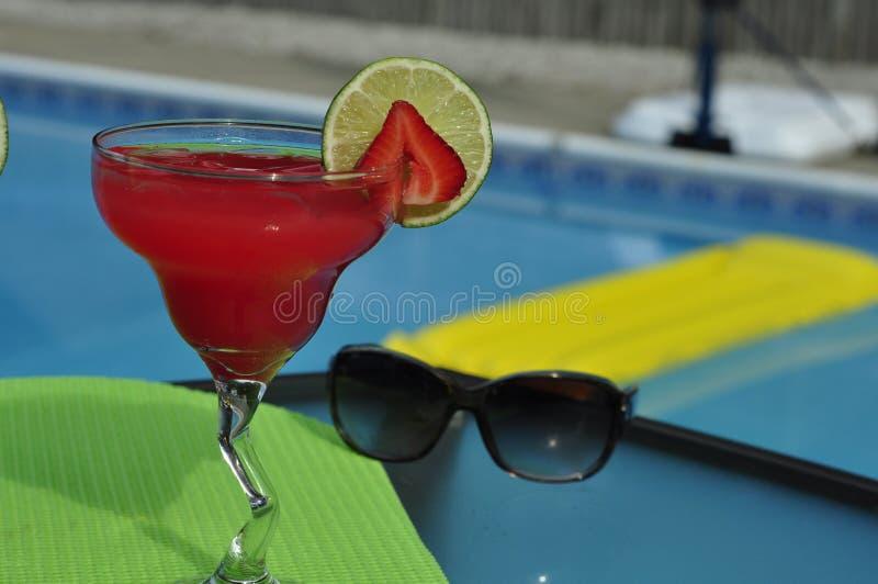 在岩石的游泳池边草莓玛格丽塔与太阳镜 库存图片