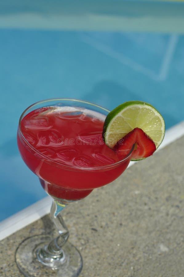 在岩石的游泳池边草莓玛格丽塔 免版税图库摄影
