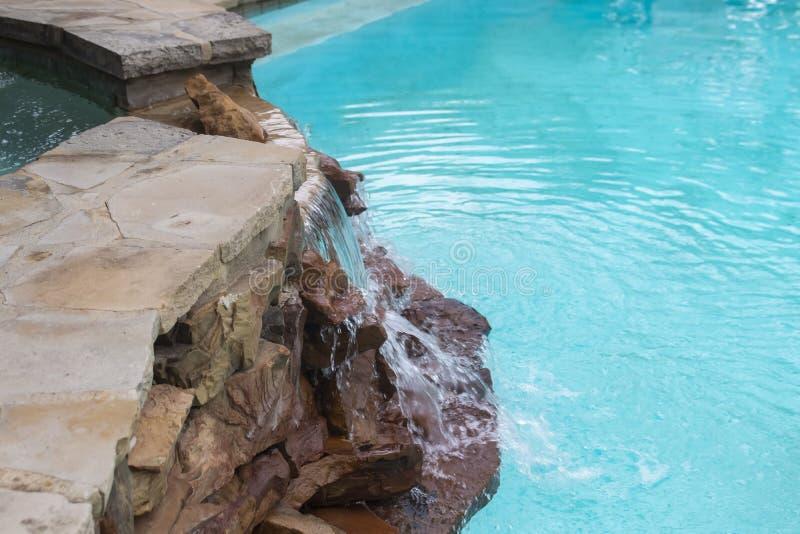 在岩石的瀑布从在高水平下来的浴盆对游泳池-刷新和在一个夏日冷却 免版税库存照片