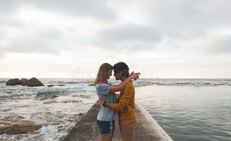 在岩石的白种人夫妇身分在海滩附近 库存图片