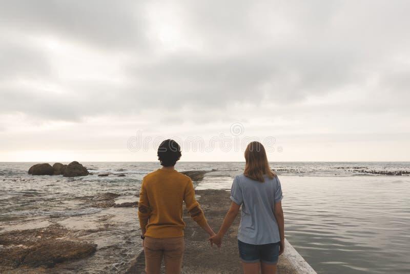 在岩石的白种人夫妇身分在海滩附近 库存照片