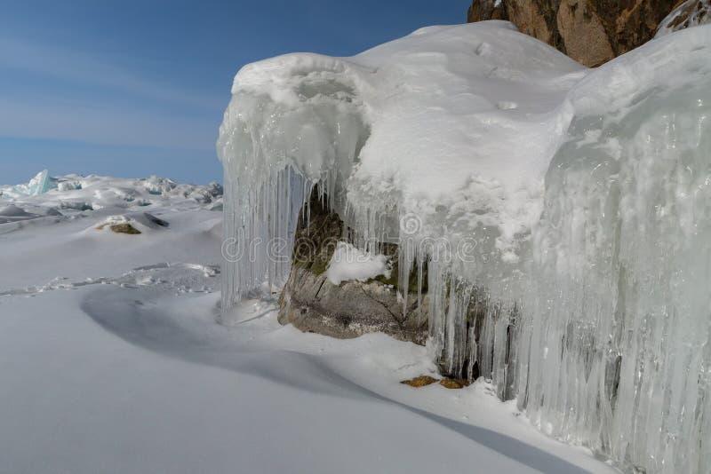 在岩石的美好的冰柱 冬天风景在贝加尔湖 免版税库存照片