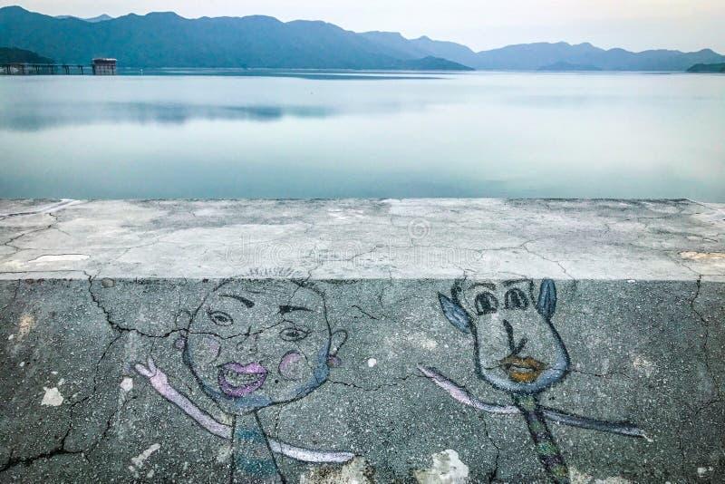 在岩石的街道画凹道在水水坝和山附近 免版税库存照片