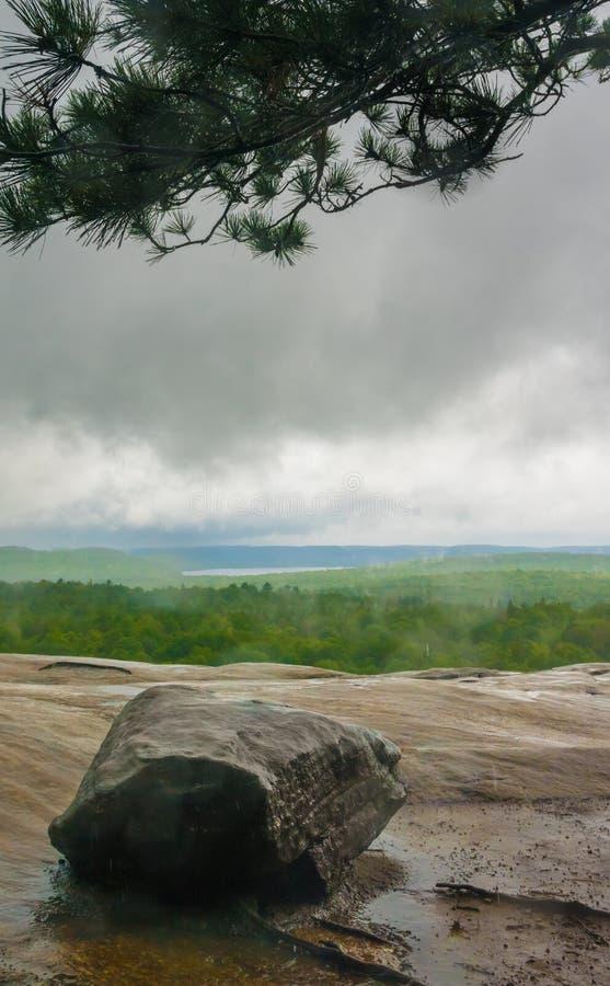 在岩石的雨天在森林里,有垂悬在场面的黑暗的云彩的看法和森林 库存照片