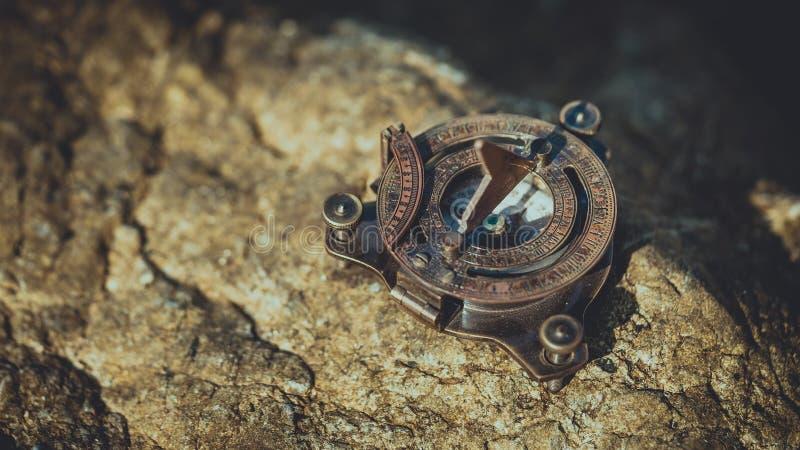 在岩石石头的葡萄酒古铜色指南针 免版税库存图片