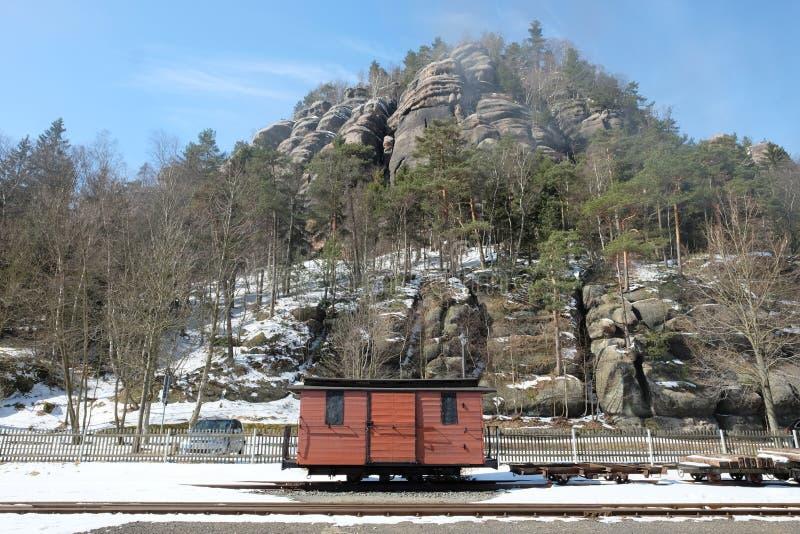 在岩石背景前面的一列小老火车 免版税图库摄影