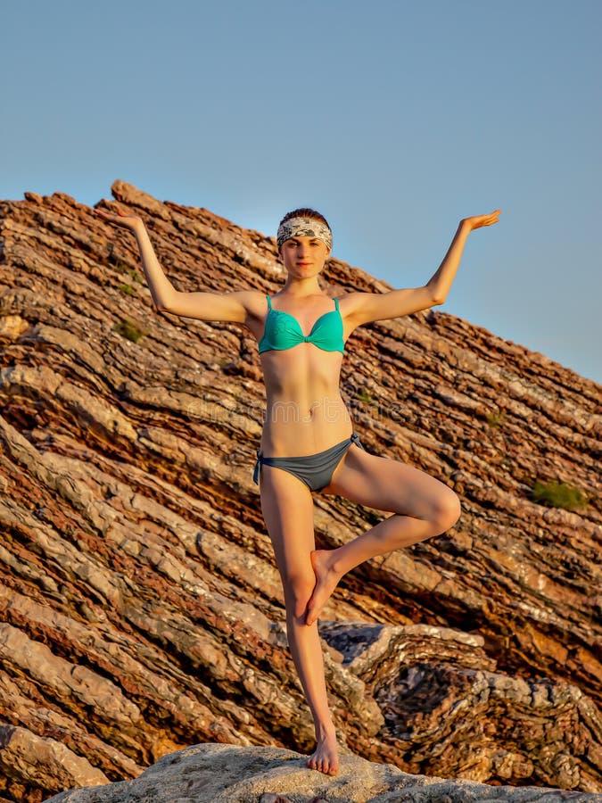 在岩石背景的女孩凝思在日落期间 瑜伽姿势 健身和一种健康生活方式 免版税库存图片
