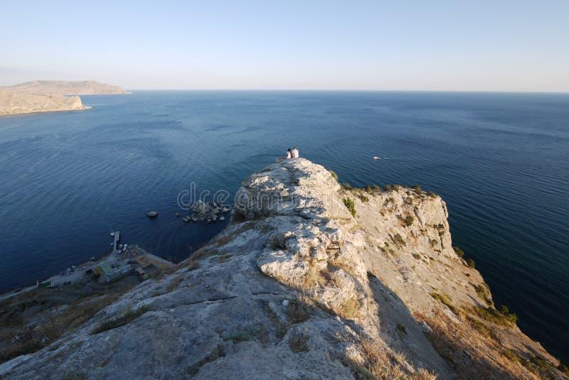 在岩石边缘的游人敬佩舒展对与漂浮在的小船的天际线的海的秀丽 免版税库存照片