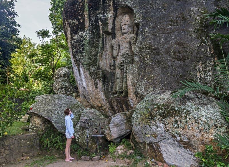 在岩石雕刻的巨大的美丽的古老雕象前面的年轻女人身分 库存照片