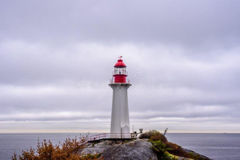 在岩石露头的灯塔在多云天空下在西温哥华,BC,加拿大 库存图片