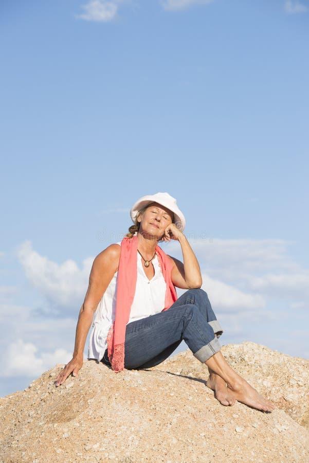 在岩石顶部的愉快的轻松的妇女 图库摄影