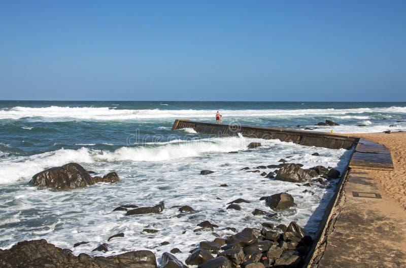 在岩石Umkomaas海滩的弯曲的具体码头 免版税库存图片
