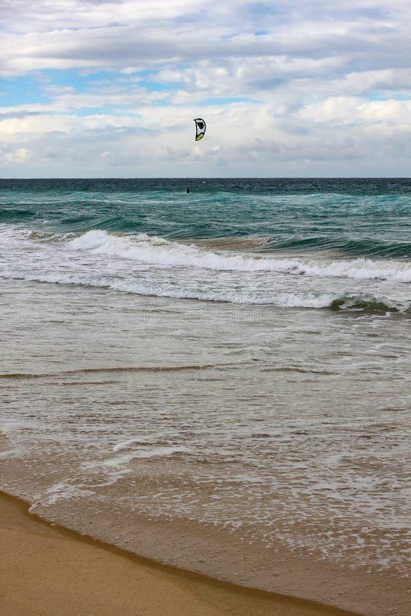 在岸上的浪潮辗压与在云彩阴影和风筝冲浪者下的天际水的垂直的 库存图片
