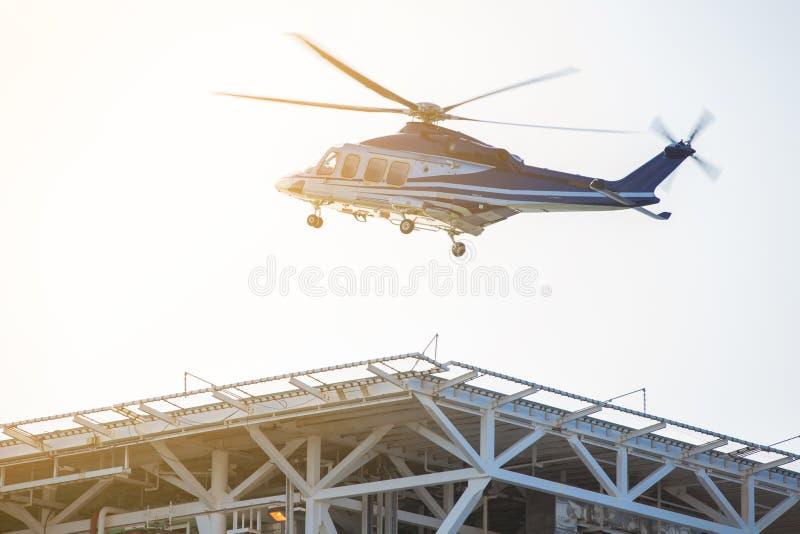 在岸之间的直升机转移的抽油装置工作者和近海处,在直升机坪的砍刀着陆在平台适应区域 免版税库存照片