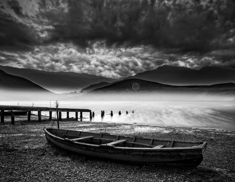 在岸湖的老小船与有薄雾的湖和山大局的 库存照片