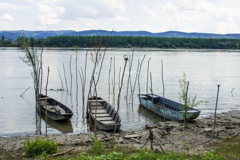 在岸的三条老生锈的小船 免版税库存照片