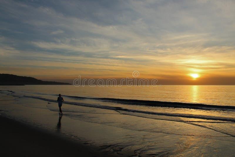在岸的慢跑者在日落在雷东多海滩,洛杉矶,加利福尼亚 图库摄影