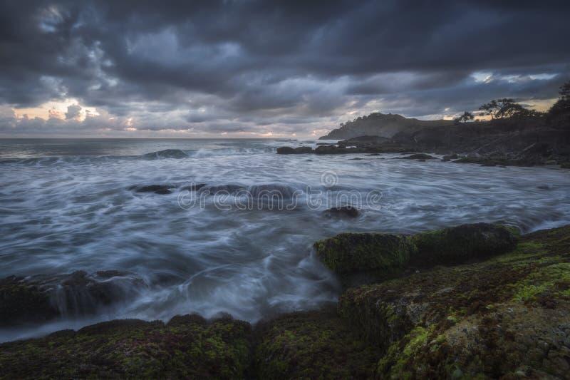 在岸的波浪断裂在黎明 图库摄影
