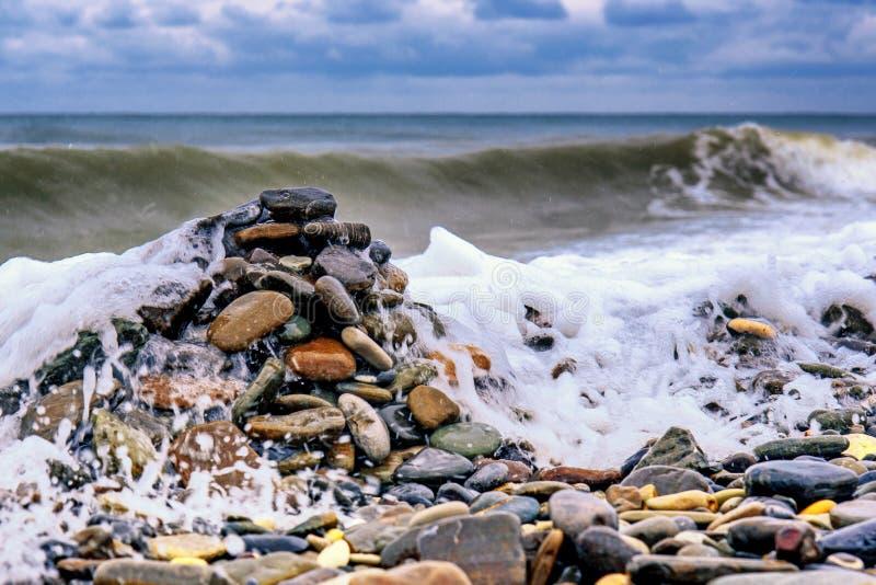 在岸的石头反对海波浪背景  免版税图库摄影