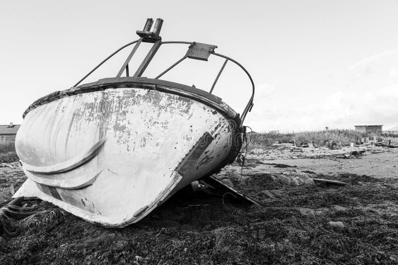 在岸的老生锈的铁小船 r 剧烈的看法 免版税库存照片