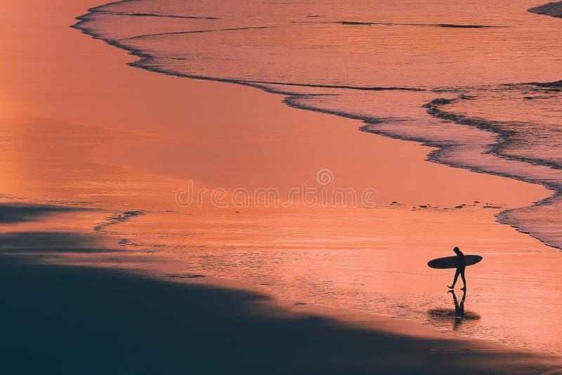 在岸的遥远的冲浪者剪影在日落 免版税库存照片