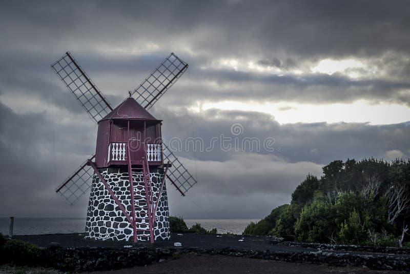在岸的风车在日出的黑暗的暴风云下在Pico海岛上 免版税库存照片