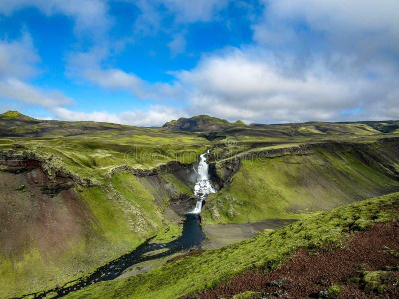 在峡谷Eldgjà ¡的史诗看法与印象深刻的瀑布和鲜绿色的青苔包括倾斜 免版税库存照片