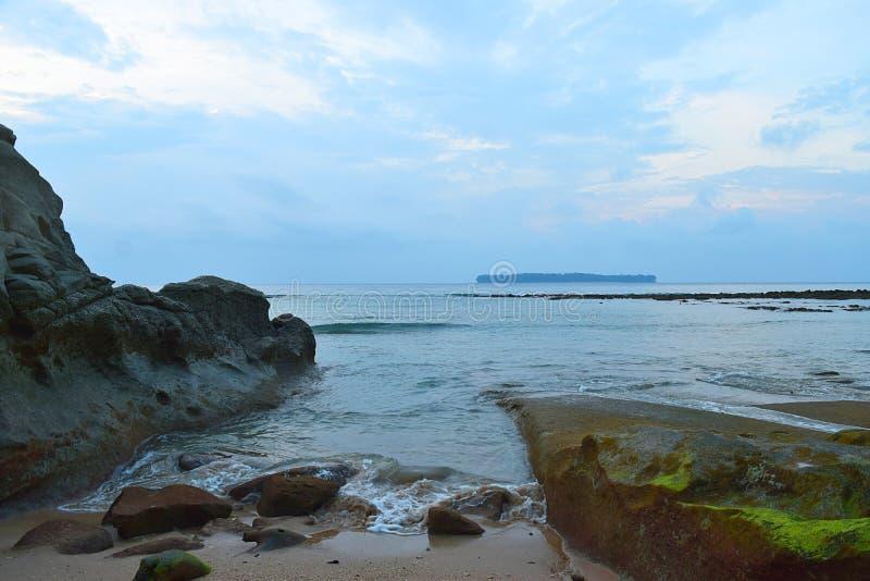 在峭壁在海滩与天空蔚蓝和海岛之间的平静的海水在距离-西塔普尔,尼尔海岛,安达曼,印度 免版税库存图片