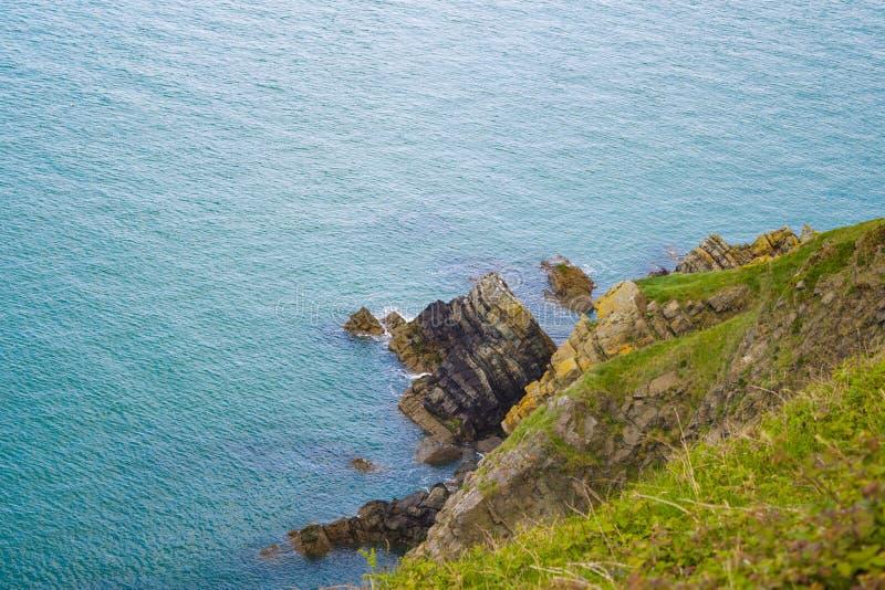 在峭壁基地的岩石露出在威克洛,爱尔兰在好日子在夏天 绿色hillslide和绿松石蓝色爱尔兰海 免版税库存图片