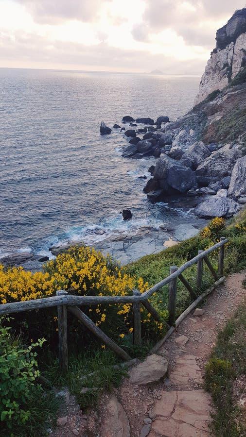在峭壁旁边的海边道路在意大利 库存照片