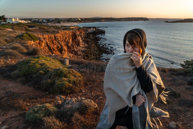 在峭壁的女孩在日落 库存照片