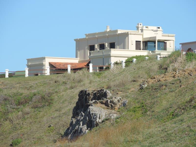 在峭壁的豪宅在海附近 库存图片