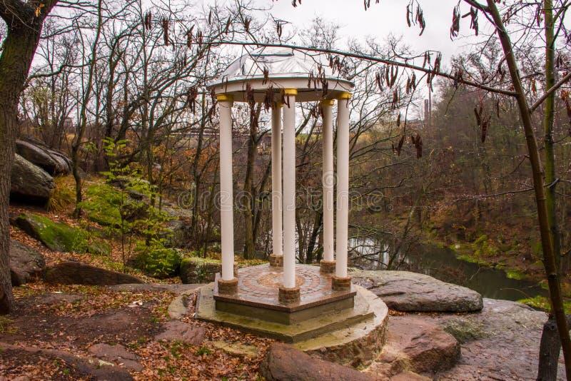 在峭壁花岗岩倾斜的偏僻的常设圆形建筑或圆的白色眺望台在树背景的与下落的叶子和河, whi的 库存照片