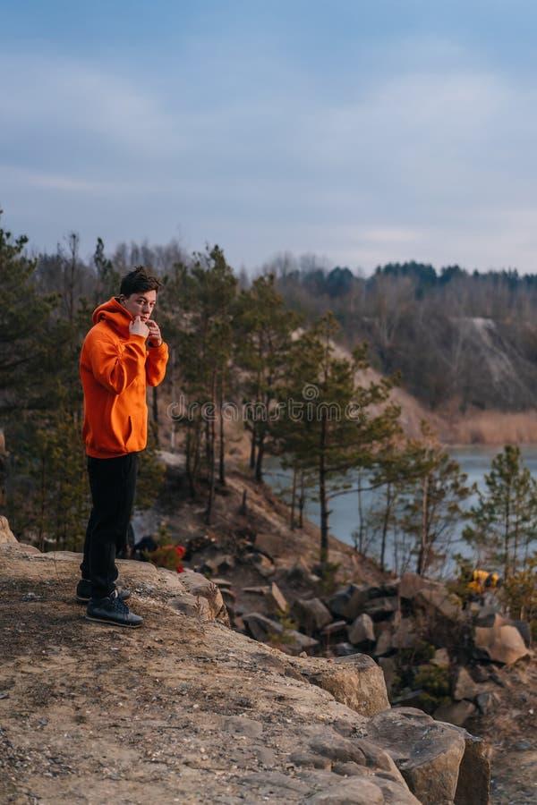 在峭壁边缘的一个年轻人身分为照相机摆在 库存图片